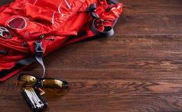 Mochila, gafas de sol y engranaje turísticos para la bicicleta en el fondo de madera Fotos de archivo libres de regalías