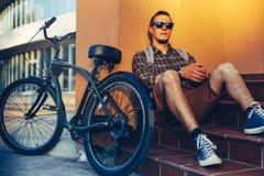Mochila hermosa de Guy Cyclist In Sunglasses With que se sienta en los pasos cerca de la bici y de la reclinación de la bicicleta foto de archivo libre de regalías