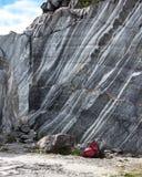 Mochila para mujer roja cerca de la roca de mármol Mina de mármol Fotografía de archivo