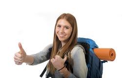 Mochila que lleva de la muchacha feliz del estudiante que da el pulgar para arriba en concepto del turismo de las vacaciones del  Imagen de archivo libre de regalías