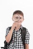 Mochila que lleva del colegial feliz y sostener la lente que magnifica imagen de archivo