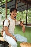 Mochila que lleva sonriente del hombre asi?tico del estudiante imagen de archivo