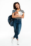 Mochila que lleva sonriente y sostener de la muchacha africana del adolescente los libros Fotografía de archivo libre de regalías