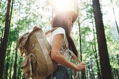 Mochila que lleva y sombrero de la mujer valiente del inconformista que viajan solamente entre árboles en bosque encendido al air imagen de archivo libre de regalías