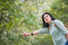 Mochileiro asiático da mulher que está na estrada do campo com árvore dentro Fotografia de Stock Royalty Free