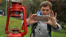 Mochileiro curioso que faz fotos da lâmpada de querosene rara em seu smartphone moderno video estoque