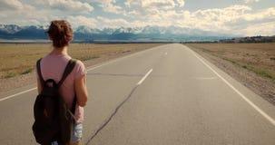 Mochileiro da jovem mulher que anda na estrada video estoque