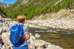Mochileiro da mulher no rio da montanha foto de stock