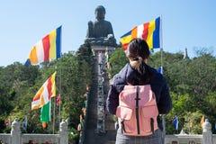 Mochileiro de viagem da jovem mulher, visita asiática do viajante Tian Tan ou Buda grande situada em Po Lin Monastery em Ngong Pi fotos de stock royalty free