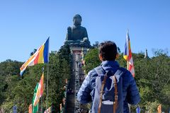 Mochileiro de viagem do homem novo, visita asiática do viajante Tian Tan ou Buda grande situada em Po Lin Monastery em Ngong Ping fotografia de stock royalty free