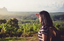 Mochileiro novo do viajante que olha para a frente no sol para ver o landscap Fotos de Stock Royalty Free