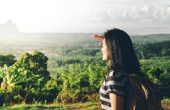 Mochileiro novo do viajante que olha para a frente no sol para ver o landscap Imagens de Stock Royalty Free