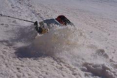 Mochileiro que desliza na neve molhada e que cai para baixo uma inclinação Fotografia de Stock