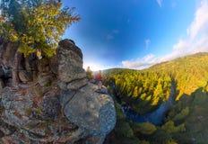 Mochileiro sobre uma queda da rocha no alvorecer Panorama largo da antena do ângulo Imagens de Stock