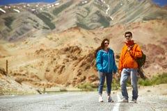 Mochileiros dos pares na estrada da montanha Imagens de Stock