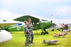 Mochishche机场,地方飞行表演,双翼飞机牦牛试验衣裳的12 M和两微笑的年轻人在葡萄酒飞机背景 免版税库存照片