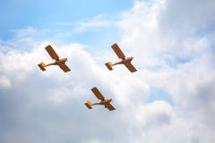 Mochishche airfield, local air showб three yellow airplanes fly together on a blue sky and white clouds background, close up stock photo