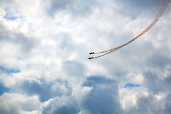 Mochishche airfield, local air show, two Yak-52, aerobatic team `Open Sky`, Barnaul, blue sky with clouds background royalty free stock image