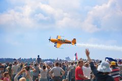 Mochishche airfield, local air show, yellow Extra EX 360 sports plane and many viewers, people watch aviashow royalty free stock photo