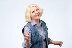 Mature woman pointing finger and toothy smile. Studio shot stock images