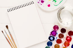 Mock up with artistic tools on white table. Notebook mock up for artwork with watercolor paints, palette, glass of water and a paintbrushes. View from above royalty free stock photo