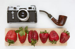 Mock up for artwork with old camera, red strawberries and smoking pipe. Top view. Place for text. Stock Photos