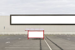 Mock up. Big horizontal supermarket or store billboard and shoping trolley bay in a parking lot. Stock Photo