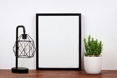 Mock up black frame against white wall with cactus and lamp on a wood shelf. Mock up black frame, cactus plant and industrial style lamp on a shelf or desk. Wood Stock Image