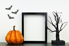 Free Mock Up Black Frame With Halloween Pumpkin And Spooky Tree Decor On A Shelf Against A White Wall Royalty Free Stock Photo - 158375775