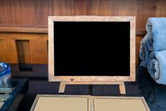 Mock up blank advertising black board with standing on black table in cafe and bar restaurant for display or montage of design royalty free stock photo