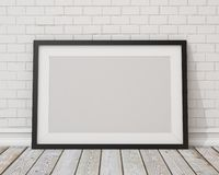 Mock up blank black horizontal picture frame on the white concrete wall and the vintage floor. Blank black horizontal picture frame on the white concrete wall Royalty Free Stock Photography