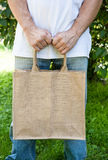 Mock-up blank cotton bag holding by man. Outdoor royalty free stock image
