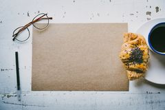 Mock-up blank craft sheet of empty paper, pen, eye glasses and morning coffee cup with croissant on white wooden desk. Business background for letter writing Stock Photography