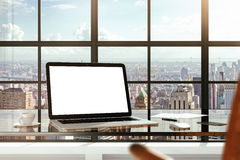 Mock up of blank laptop on the desk in office Royalty Free Stock Image