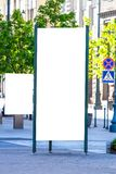 Mock up. Blank outdoor advertising column and billboard stand outdoors, public information board in the city. Stock Photo