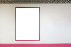 Mock up blank poster frame with pink frames hanging on wall in shopping mill. Mock up blank advertising poster frame with pink frames hanging on wall in shopping Stock Images
