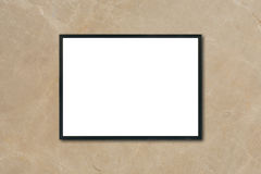 Mock up blank poster picture frame hanging on brown marble wall in room Stock Photography