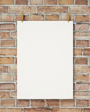Mock up blank white hanging poster with clothespin and rope on brick wall, background. Blank white hanging poster with clothespin and rope on brick wall Royalty Free Stock Image