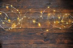 Mock up Christmas lights garland on wooden background with place for your text. Flat lay, top view photo mock up.  Stock Photo