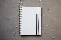 Mock-up with clean notepad and small white flowers, top view. Flat lay of blank notebook and pencil, copy space stock photo