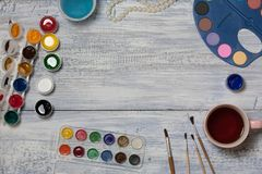 Mock up. Creative space. Artist workspace on vintage wooden table: watercolor, gouache paints, paint brushes and water.  stock photos