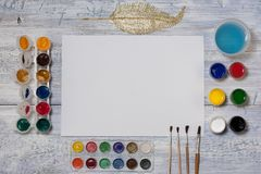 Mock up. Creative space. Artist workspace on vintage wooden table: watercolor, white paper, paint brushes, gouache paints, water a. Nd beads royalty free stock photography