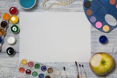 Mock up. Creative space. Artist workspace on vintage wooden table: watercolor, white paper, paint brushes, gouache paints, water, royalty free stock images
