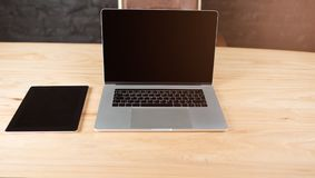 Mock up with digital tablet and net-book. Workplace with gadgets. Touch pad and open laptop computer with blank copy space screen lying on a wooden table in Royalty Free Stock Images