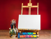 Mock up easel palette watercolors and brushes with empty white canvas royalty free stock photography