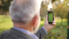 Mock up of elderly man using phone outside. Green screen. Back view of man holding phone at harm`s length. Grandpa