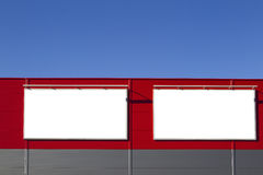 Mock up. Empty horizontal billboards screens on the red wall against blue sky Royalty Free Stock Photography