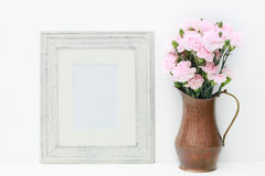 A mock up of a empty white frame and flowers. A white background displays an empty white wooden frame with a copper vase and miniature pink carnations. Add your Stock Images