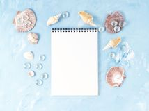Mock up with frame of seashell, notepad on blue stone backdrop, copy space. Summer concept of holiday by sea. Mock up with frame of seashell and notepad on blue Royalty Free Stock Images