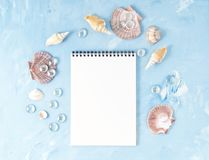 Mock up with frame of seashell, notepad on blue stone backdrop, copy space. Summer concept of holiday by sea. Mock up with frame of seashell and notepad on blue Royalty Free Stock Photo